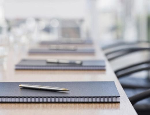 Neatly laid stationary on conference table.