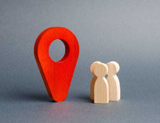 Location icon and small people wooden figures.