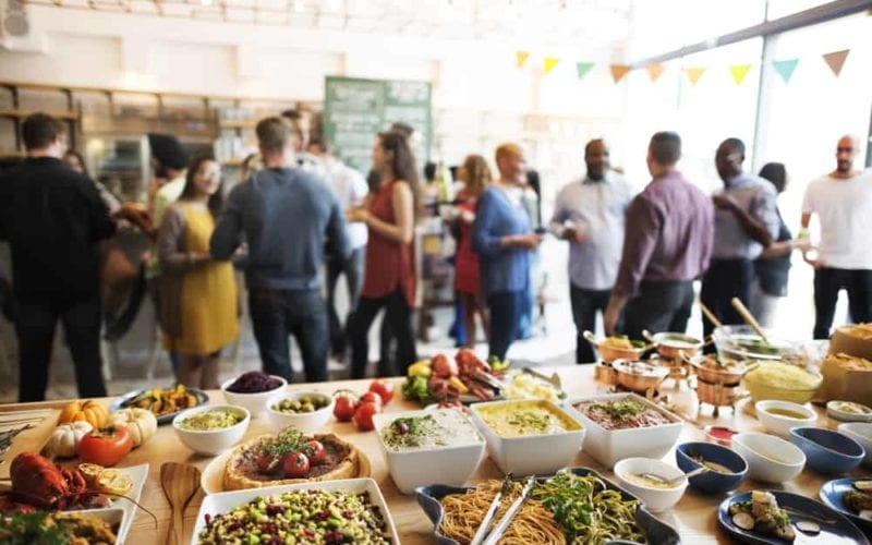Multi-cultured buffet, with a crowd of mingling people.