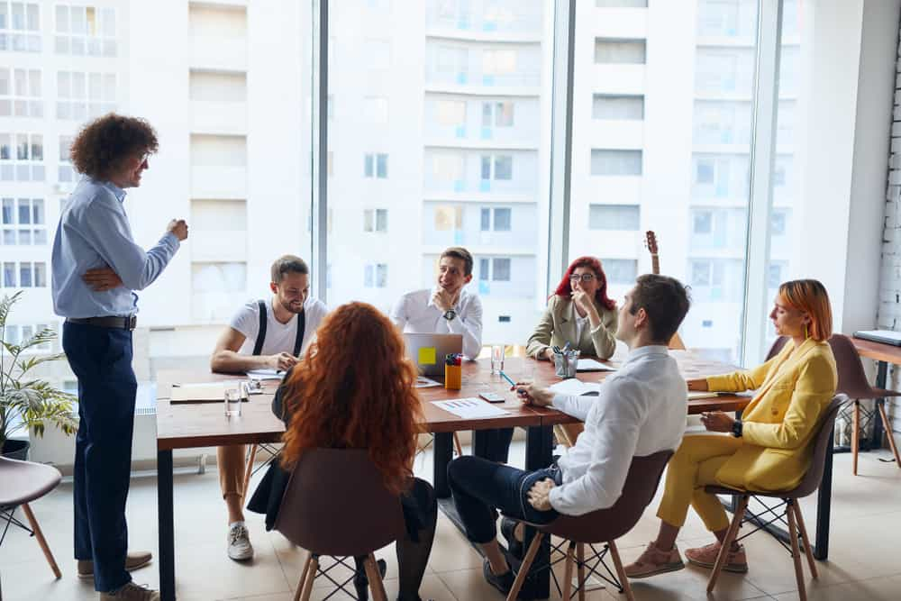 seven young business people taking a meeting