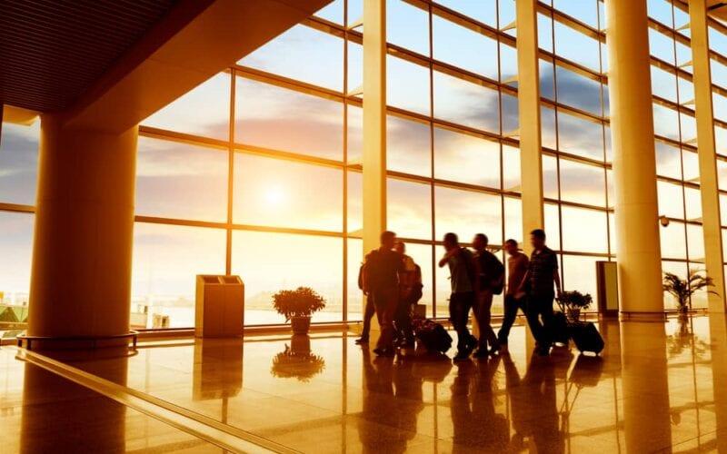 Travellers commuting through an airport at sundown.